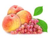 Red grape and peachs with green leaf — Stock Photo