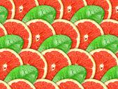 Fundo de fatias de grapefruit e folha verde — Foto Stock