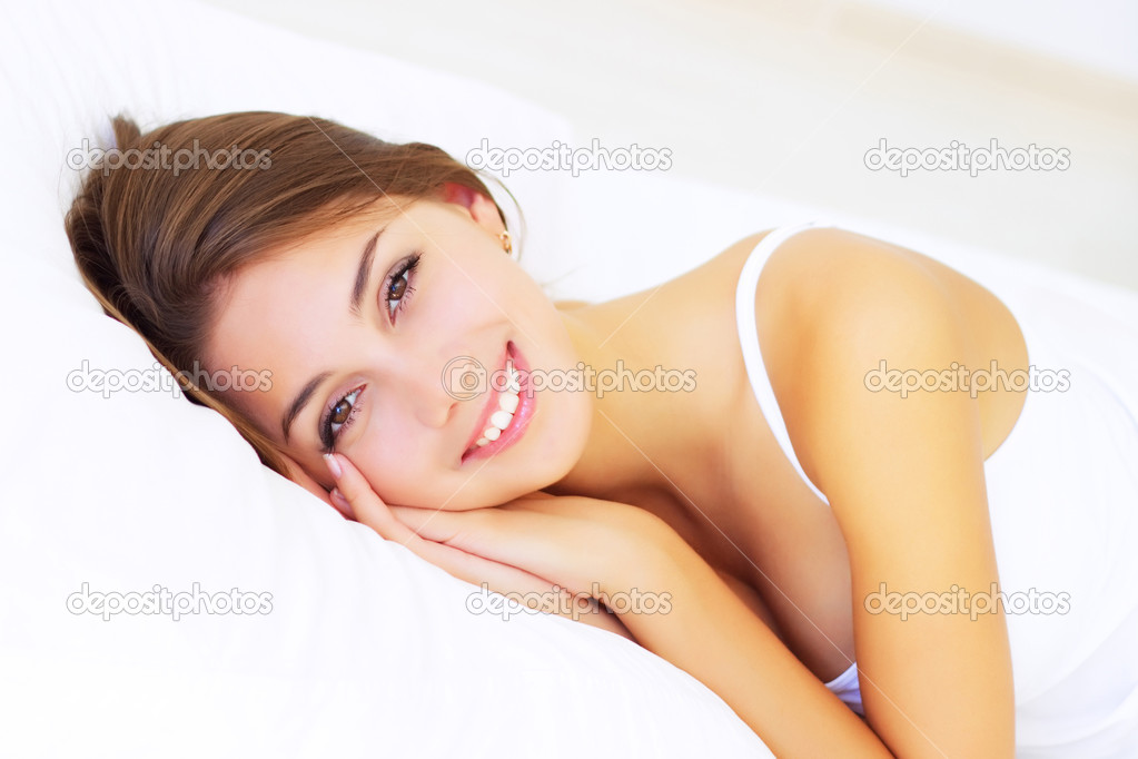 Smiling girl lying on the bed — Stock Photo #10113895