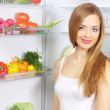 Picking food from fridge. Vegetables in the refrigerator — Stock Photo #8734345