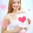 Smiling girl with valentine card — Stock Photo