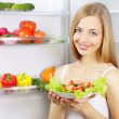 Young woman with healthy salad. background refrigerator - Zdjęcie stockowe