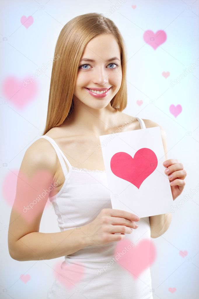 Smiling girl with valentine card on a blue background — Stockfoto #8750284