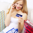 Girl with mobile phone and credit card - Stock Photo