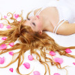 Pretty girl with rose petals in her hair — Stock Photo