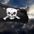 Jolly Roger (pirate flag) against storm clouds — Stock Photo #8283391