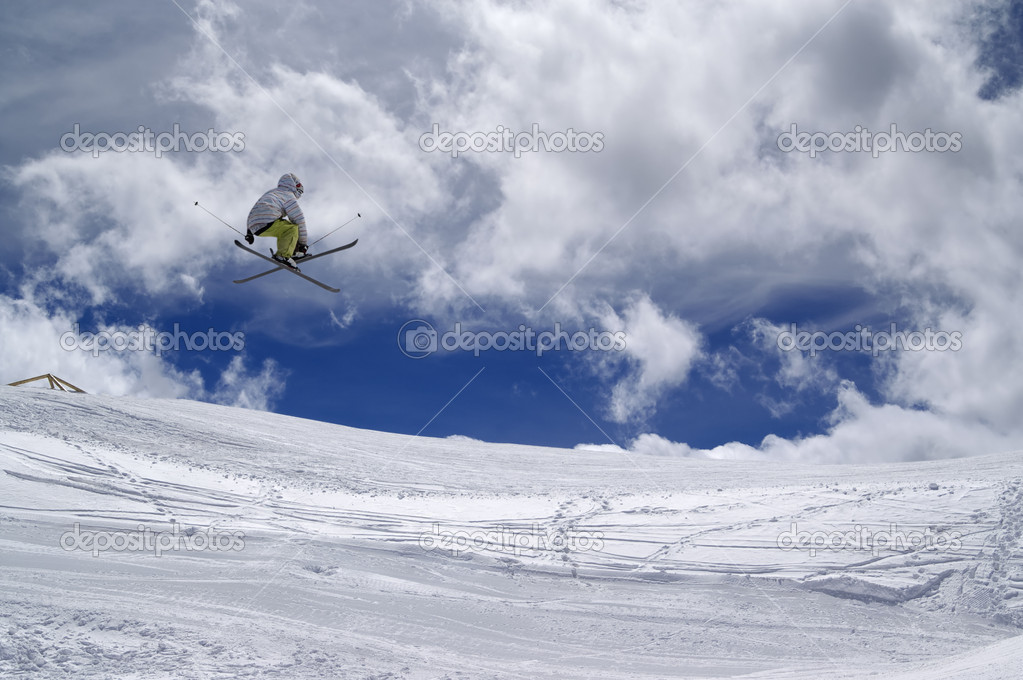Freestyle ski jumper with crossed skis against cloudy sky — Stock Photo #8769433