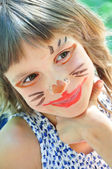 Happy child with funny painted face — Stock Photo