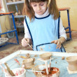 Child girl shaping clay in pottery studio — Stock Photo
