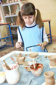 Child girl shaping clay in pottery studio — 图库照片