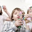 Children blowing bubbles — Stock Photo #9413634