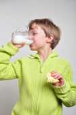 Child boy eating cake and drinking milk — Stock Photo
