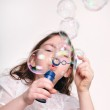Child blowing bubbles with bubble wand — Stock Photo #9449994