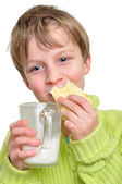 Child eating cake and drinking milk — Stock Photo