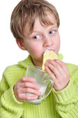 Child eating cake and dringking milk — Stock Photo