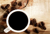 Coffee beans with white cup over wooden desk — Stock Photo