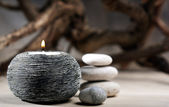 Burning candle with pebbles. abstract still life — Stockfoto