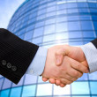 Business accounting balance. Handshake with modern skyscrapers as background. - Stock Photo