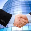 Foto de Stock  : Business accounting balance. Handshake with modern skyscrapers as background.