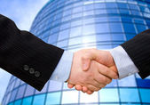 Business accounting balance. Handshake with modern skyscrapers as background. — Stock Photo