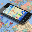 Stock Photo: Smartphone with GPS navigation on world map