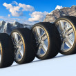 Set of car wheels in snowy mountains - Stock Photo