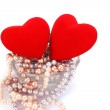 Red hearts and necklase in vase — Stock Photo