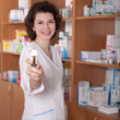 Young chemist showing bottle of pills — Stock Photo