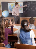 小学校低学年の生徒の前で男性教師 — ストック写真
