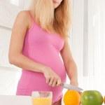 Pregnant woman cutting orange — Stock Photo #8404023