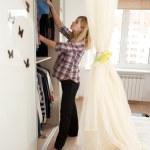 Pregnant blonde near wardrobe — Stock Photo