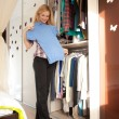 Choosing dress near wardrobe — Stockfoto