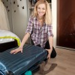 Young blonde packing travel bag — Stock Photo