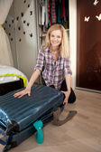Young blonde packing travel bag — 图库照片