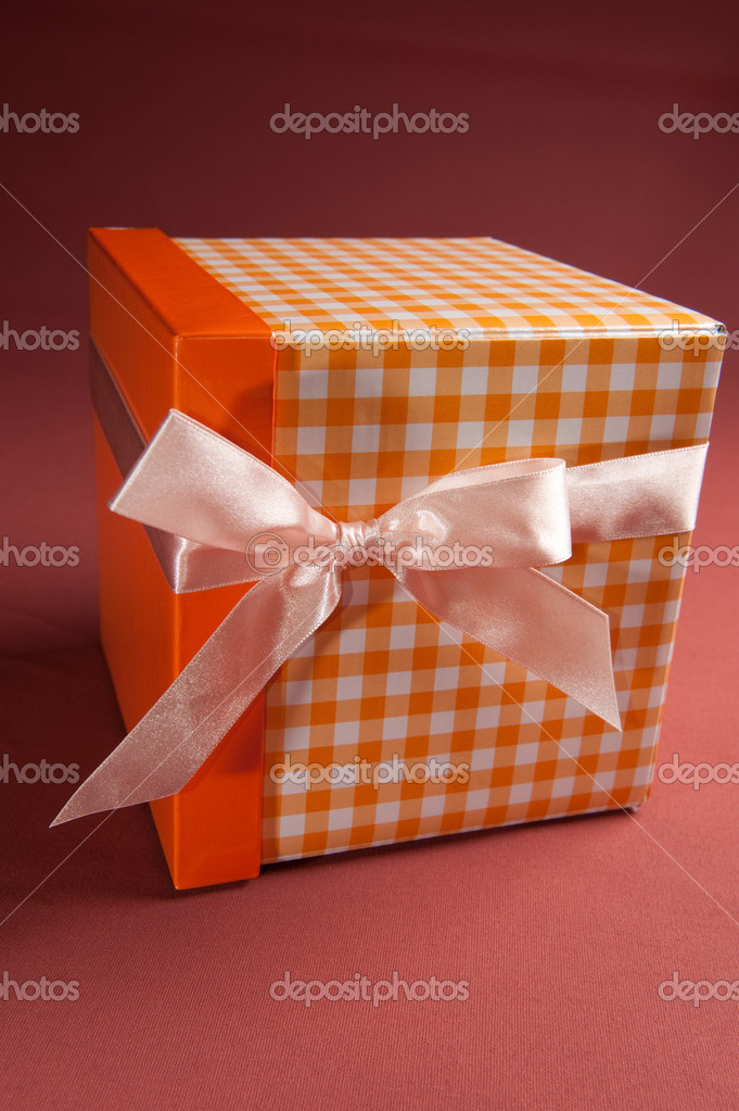 Orange present box with pink bow on textile background — Stock Photo #8691873