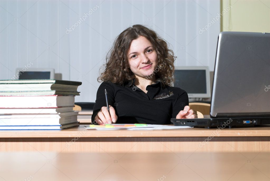 Confident female student is waiting for something and playing with her pen.  Stock Photo #8738338