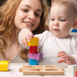 Mother and baby daughter building tower — Стоковое фото