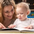 Mother and baby reading - Stock Photo
