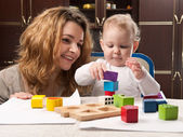 Mother and baby daughter building tower — Stock Photo