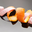 Orange peel and measuring tape — Stock Photo