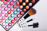 Colorful lip gloss palette with set of brushes — Stock Photo