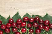 берри черри с листьями на деревянных фоне — Стоковое фото