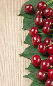 Berry Cherry with leaves on wooden background — Stock Photo