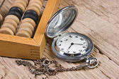 Pocket watch and abacus — Stock Photo