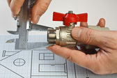 Plumbing fittings in hand on drawing — Foto de Stock