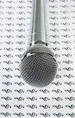 Microphone on background of the treble clef — Stock Photo