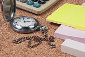 Pocket watch and scratch paper on a cork board — Stock Photo