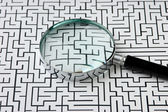 Magnifying glass and labyrinth — Stock Photo