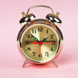Golden alarm clock on a color background — Stock Photo #8541778