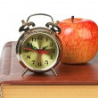 Golden alarm clock and apple on the book isolated — Stock Photo #8567719